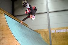 Un inline skater esegue un handplant su una miniramp.