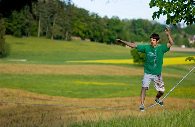 Junger Mann beim Balancieren auf einer Slackline Outdoor.