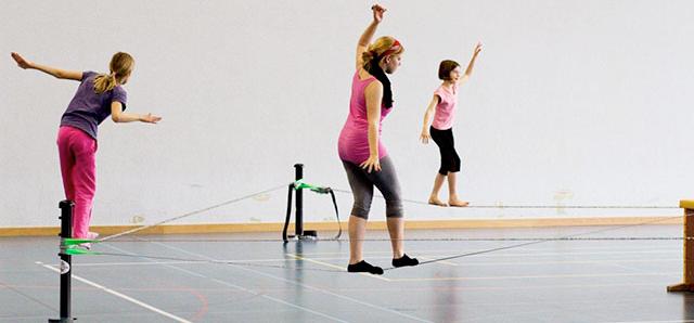 Junge Mädchen balancieren auf drei Slacklines.