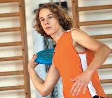 Un jeune homme lance un frisbee dans une salle de sport.