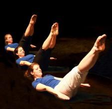 Trois personnes sont assises sur le sol, les jambes tendues vers le haut, les bras le long du corps et la tête et les épaules relevées.