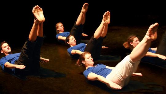 Vier Personen bei einer Pilates-übung.