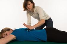 Una donna massaggia con una mano la schiena di un'altra persona sdraiata bocconi