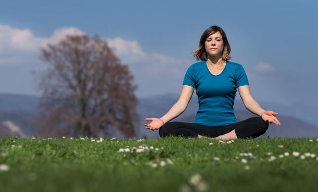 Une jeune femme est assise en position de tailleur, le dos des mains posé sur les genoux et les yeux fermés.