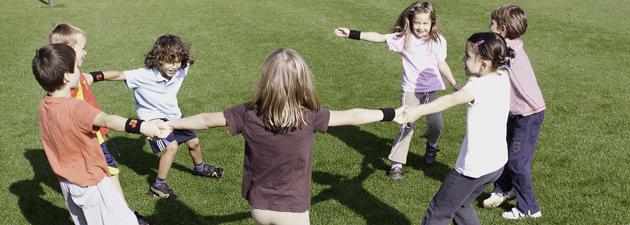Dei bambini formano un cerchio ed eseguono dei movimenti con le braccia