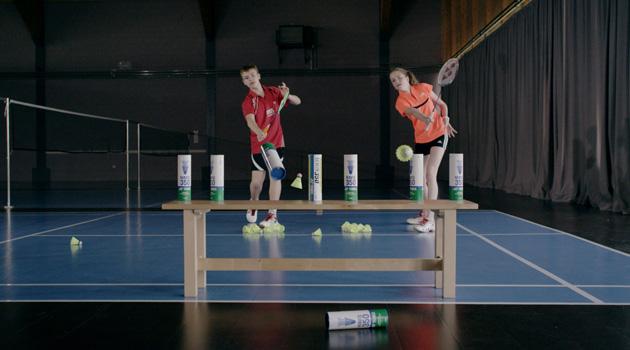 Un garçon et une fille vise des cibles sur un banc avec une raquette et un volant.