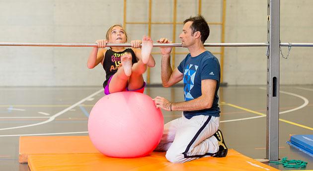 Auf einem Gymball sitzend, schwingt sich eine Schülerin unter einer Reckstange durch. Der Sportlehrer kniet daneben, bereit, im Bedarfsfall einzugreifen.