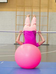 Assise sur un swissball, une jeune fille effectue une montée au ventre à la barre.