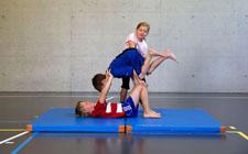 Une jeune fille aide un garçon à monter à l'appui sur un second camarade couché sur le dos.