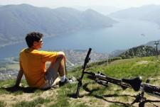Mann sitzt an schöner Ausscihtslage auf Hügel und schaut auf einen See.