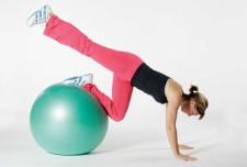 Athletin führt eine Übung auf dem Swissball aus.