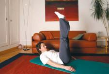 """eine Frau auf einer Gymnastikmatte im Wohnzimmer bei einem """"Klappmesser""""."""