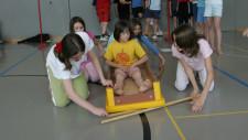 Una bambina è seduta in ultimo elemento di cassone rovesciato e quattro compagne la spingono