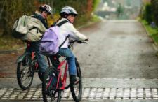 Zwei Mädchen beim Velofahren auf der Strasse.