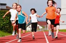Des enfants courent sur une piste d'athlétisme.
