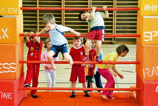 Mehrere Kinder klettern an einem Gerüst.