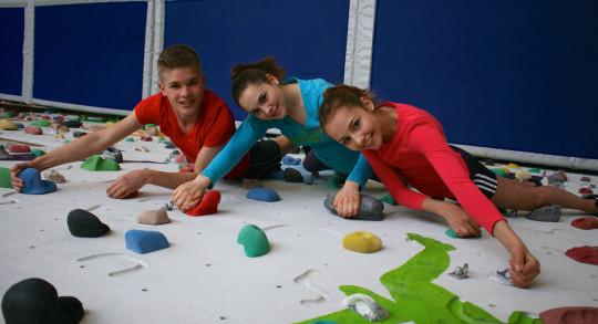 Drei Jugendliche an einer Kletterwand.