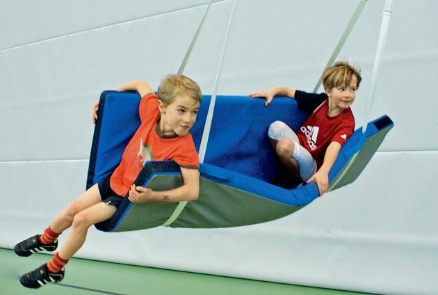 Deux enfants se balancent sur un tapis tenu par des sangles.