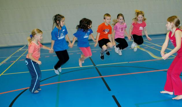 Mehrere Kinder im Halbkreis springen gemeinsam hoch.