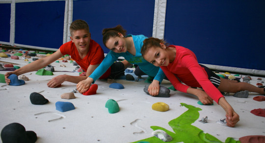 Trois jeunes  grimpent sur un mur d'escalade.