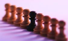 Foto simbolica: un pedone nero in mezzo ad una fila di pedoni bianchi su una scacchiera