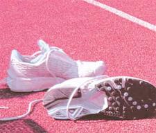 Foto simbolica: delle scarpe da tennis bianche su un campo da tennis di terra battuta