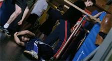 Nella foto un giovane si accanisce su un altro rannicchiato a terra mentre altri ragazzi guardano senza intervenire