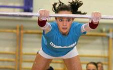 Une gymnaste se balance à la barre fixe.