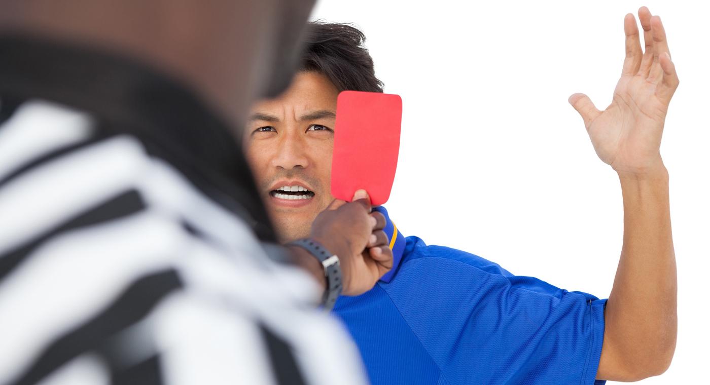 Foto: un arbitro mostra il cartellino rosso a un giocatore che si arrabbia moltissimo
