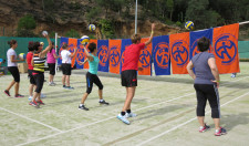 Foto: Frauen beim Werfen von Bällen auf Badetücher, die auf Volleyball-Netz hängen.
