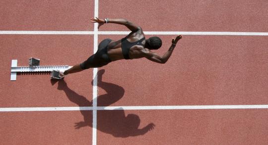 Eine Athletin startet vom Startblock. Luftaufnahme.