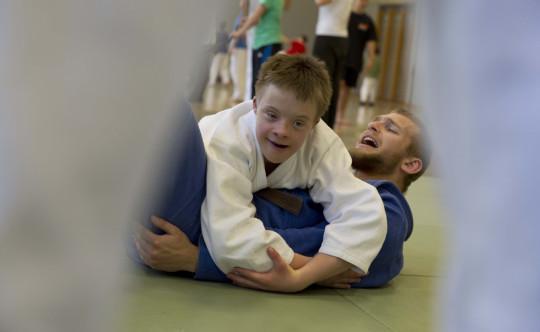 Jugendlicher mit geistiger Behinderung legt beim Judo seinen Lehrer auf den Boden.