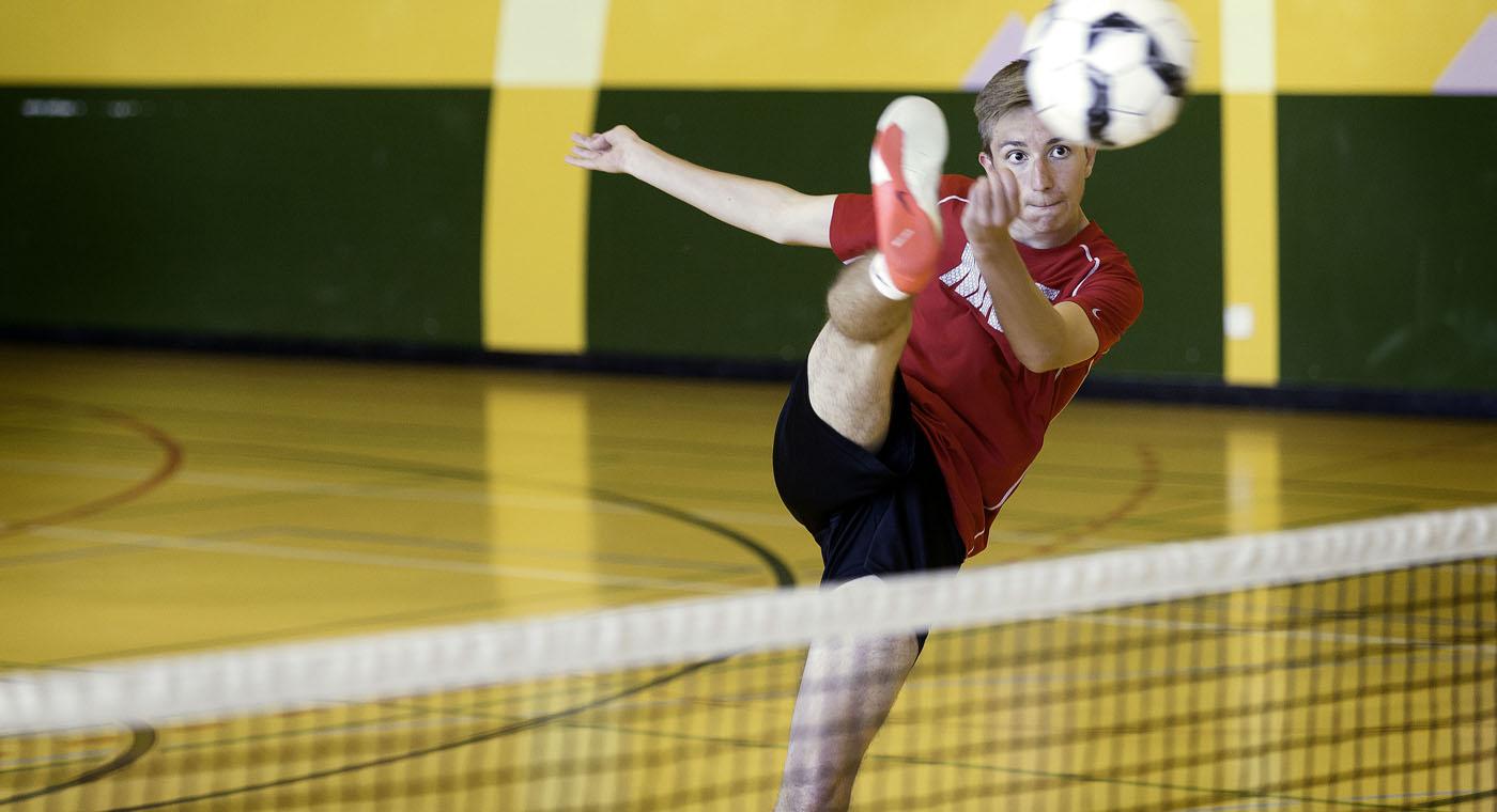 Un jeune frappe le ballon par-dessus le filet.