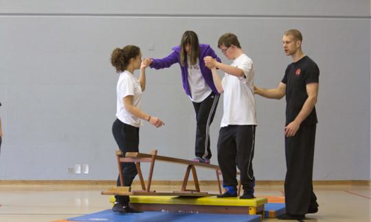 Foto: Jugendliche mit und ohne Behinderung bei einer Übung auf der Langbank.