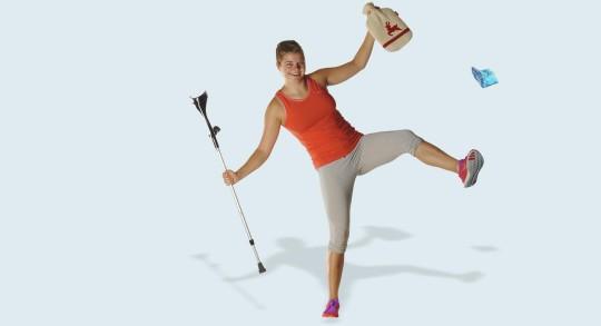 Junge Frau mit Krücken steht auf einem Bein und lächelt