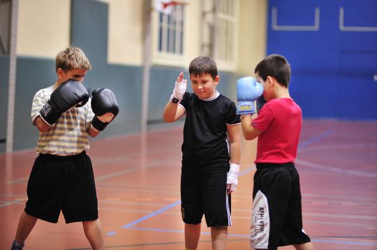 Deux boxeurs s'apprêtent à combattre sous la direction d'un camarade.
