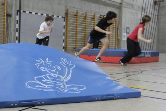 Dei bambini corrono in una palestra disseminata di tappetini e tappetoni