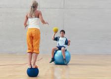 Une fille est debout en équilibre sur un medecine ball et s'apprête à attraper un ballon lancé par un camarade assis sur un ballon de gymnastique.