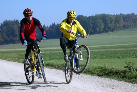 Zwei erwachsene Männer beim Mountainbike-Fahren auf einem Feldweg.