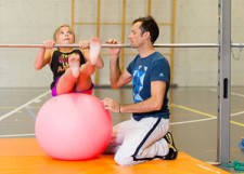 Unter dem wachsamen Auge einer Lehrperson führt ein Mädchen eine Übung an Reckstange, sitzend auf einem Gymnastikball aus.