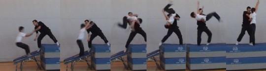 Lehrperson hilft Schüler beim Salto vorwärts auf dem Minitrampolin.