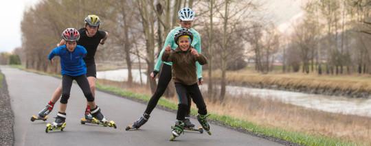 Foto: Vier Kinder und Jugendliche auf Inlineskates und Rollskiern.
