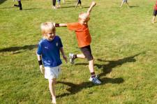 Kinder hüpfen auf einer Wiese umher.
