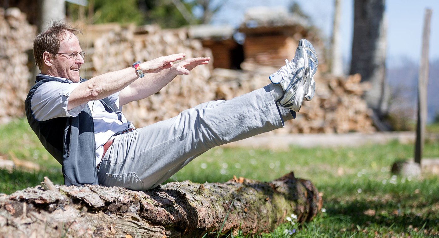Ein Mann sitzt auf einem Baumstamm und führt eine Bauch/Bein-Übung durch.