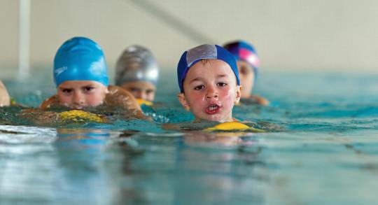 Mehrere Kinder beim Schwimmen mit einem Tauchring.