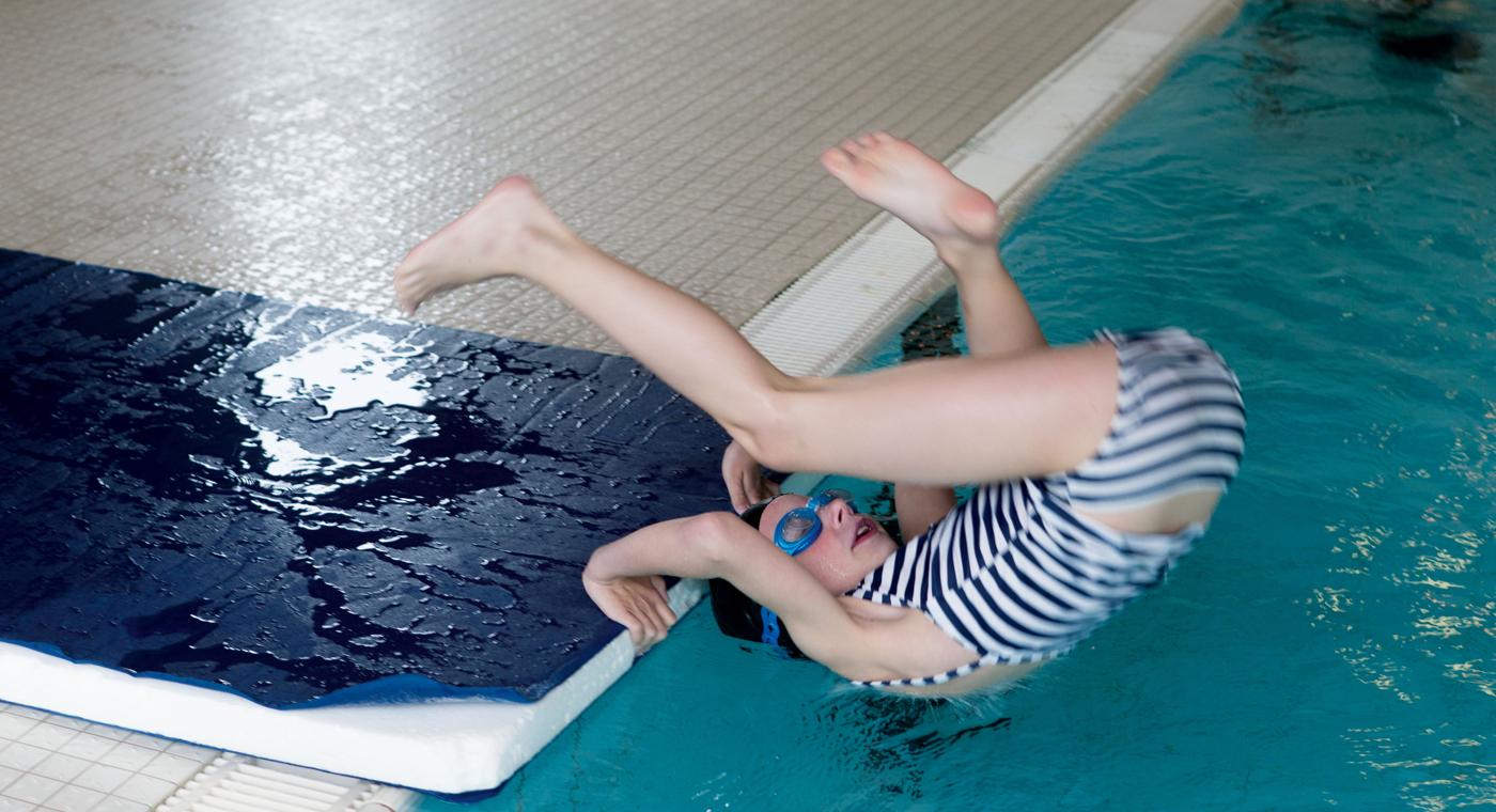 Une jeune fille effectue une roulade en avant depuis le bord du bassin.
