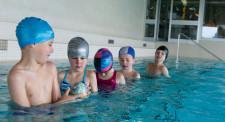 Foto: dei bambini sono disposti in fila indiana in acqua e si passano una palla