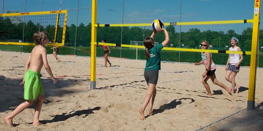 Quatre enfants jouent au beach-volley sur un petit terrain.