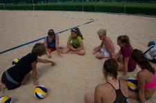 Un'insegnante, circondata da un gruppo di giovani, disegna delle direttive sulla sabbia