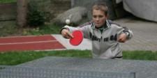 Foto: un bambino mentre gioca a ping pong in un giardino